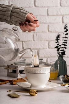 Derramando ervas de chá na xícara
