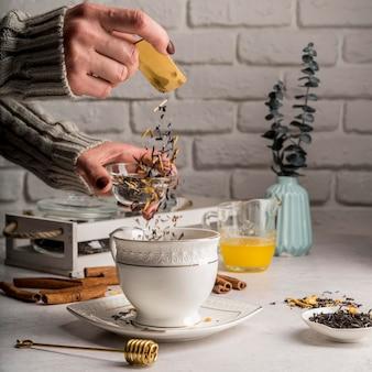 Derramando ervas de chá