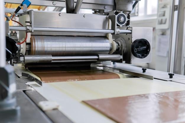 Derramando folhas de wafer com uma fina camada de chocolate na esteira de uma fábrica de confeitaria