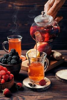 Derramando frutas acabadas de fazer e chá de ervas da chaleira no copo
