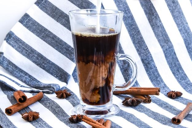 Derramando leite em copo com café frio em cinza com canela e anis, café com leite