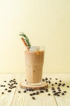 Derramando leite em copo de café preto com cubo de gelo, canela e alecrim no fundo de madeira