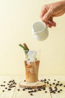 Derramando leite em um copo de café preto com cubo de gelo, canela e alecrim na mesa de madeira