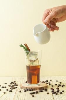 Derramando leite em um copo de café preto com cubo de gelo, canela e alecrim na superfície de madeira
