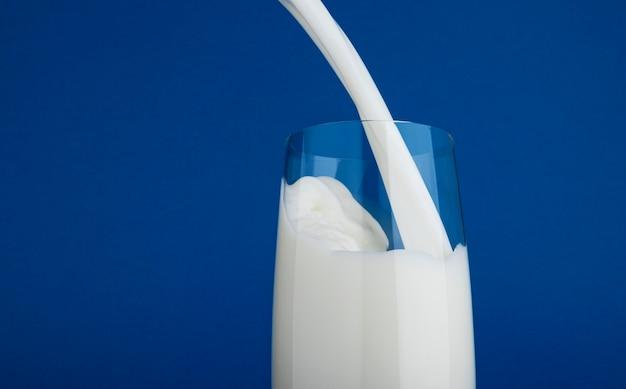 Derramando leite em vidro isolado em fundo azul