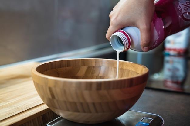 Derramando leite manualmente em uma tigela de madeira colocada em cima de uma máquina de pesagem eletrônica em uma cozinha