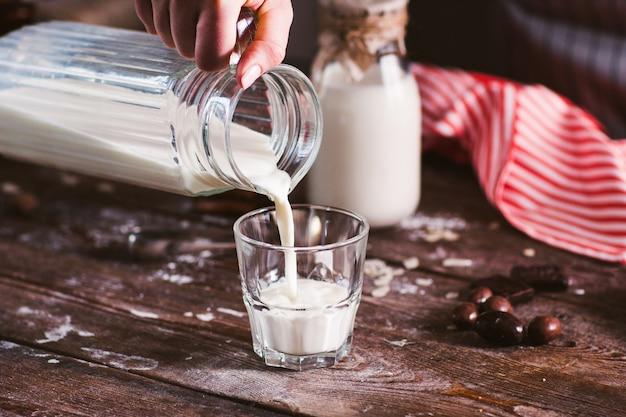 Derramando leite novo em close up de vidro.