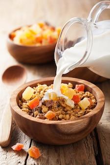 Derramando leite sobre granola saudável com frutas secas no café da manhã