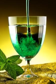 Derramando líquido verde em um copo de vidro
