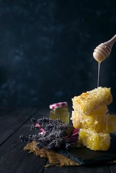 Derramando mel em pente de mel com flores de lavanda em fundo escuro de pedra