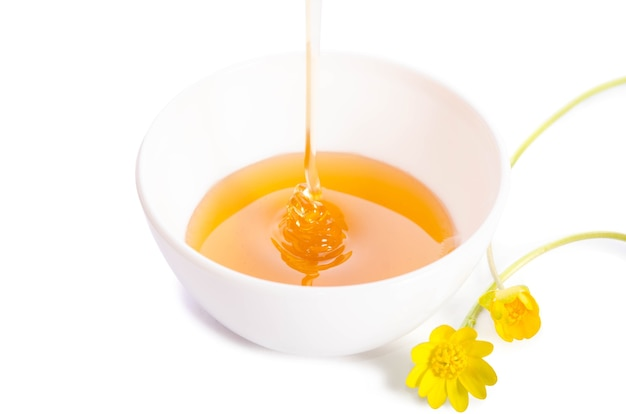 Derramando mel em uma tigela de porcelana