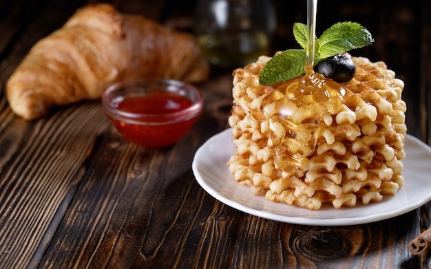 Derramando mel ou xarope em uma pilha de waffles recém-assados decorados com mirtilo e hortelã na chapa branca deliciosa massa caseira no café da manhã na mesa de madeira ou fundo rústico