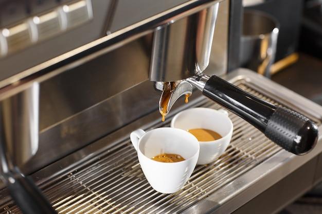 Derramando o fluxo de café da máquina profissional na xícara. barista a preparar café expresso, com porta-filtro. café moído fresco. beber café torrado pela manhã.