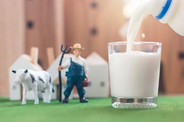 Derramando o leite no copo com modelo de figura de vaca e agricultor em miniatura na grama de simulação