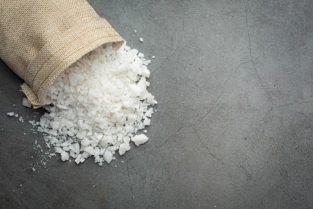 Derramando sal do saco para o chão