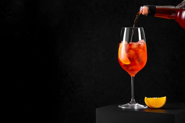 Derramando spritz cocktail em uma taça de vinho com gelo e uma fatia de laranja em fundo escuro