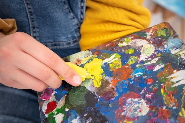 Derramando tinta à mão na paleta do pintor