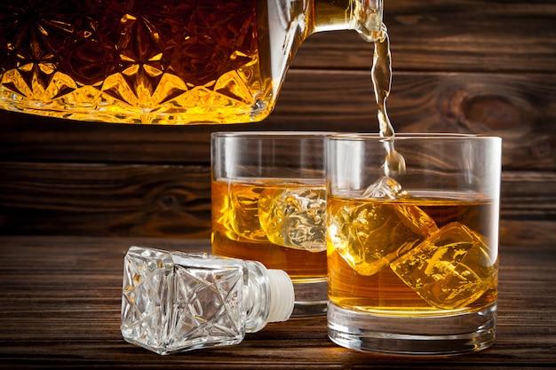 Derramando uísque da garrafa nos copos