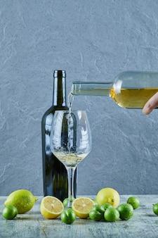 Derramando vinho branco no copo e limões, garrafa de vinho e ameixas de cereja de lado