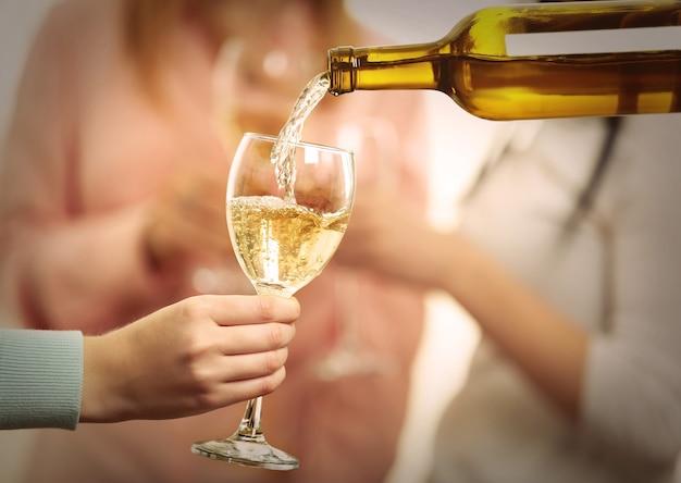 Derramando vinho branco no copo na festa da galinha, close-up