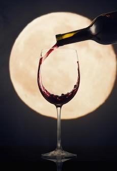 Derramando vinho tinto contra a lua