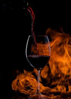 Derramando vinho tinto em vidro com haste longa, com fogo no fundo