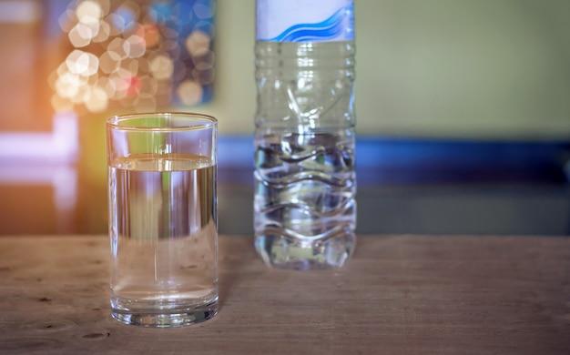 Derramar a água da bebida fresca purificada da garrafa no fundo de mesa de vidro