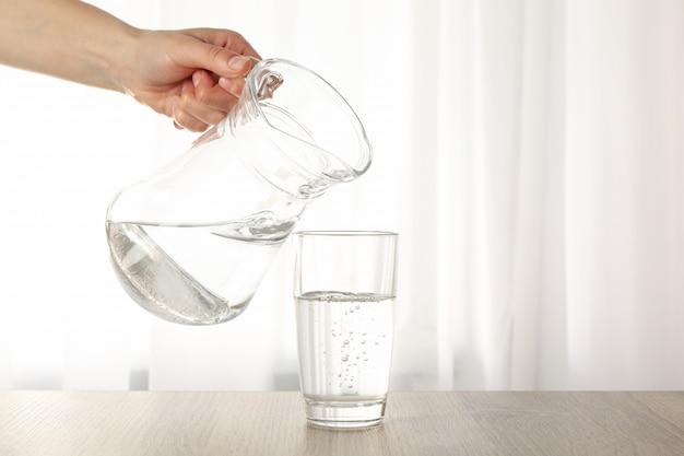 Derramar água fresca purificada do jarro em vidro na mesa de madeira