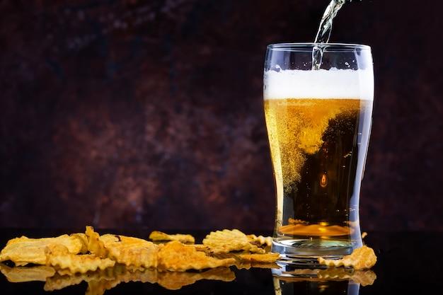 Derramar cerveja em vidro e batatas fritas no fundo escuro de madeira