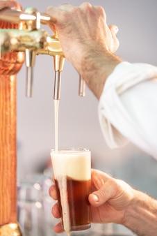 Derramar cerveja para o cliente. barman, derramando cerveja em pé no balcão do bar.
