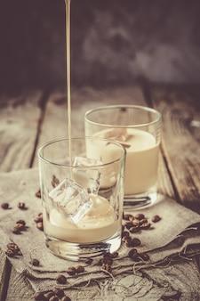 Derramar licor de café em copos com gelo e feijão