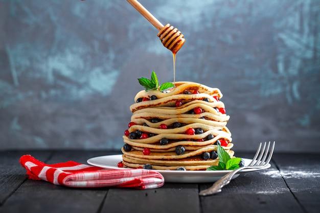 Derramar mel em panquecas caseiras douradas com frutas frescas e hortelã para delicioso café da manhã doce