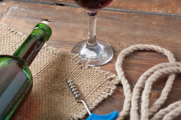 Derramar o copo de vinho vermelho contra a mesa de madeira