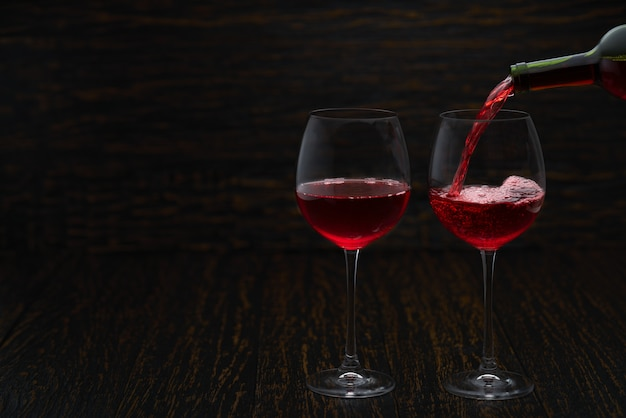 Derramar vinho tinto nos copos contra a mesa de madeira