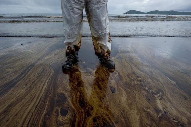 Derrame de petróleo misturado com outras substâncias químicas na superfície do mar e areia.