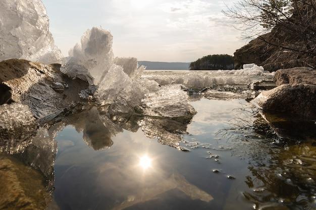 Derretimento do gelo na primavera no lago, reflexo do gelo e do sol na água, época antes do pôr do sol