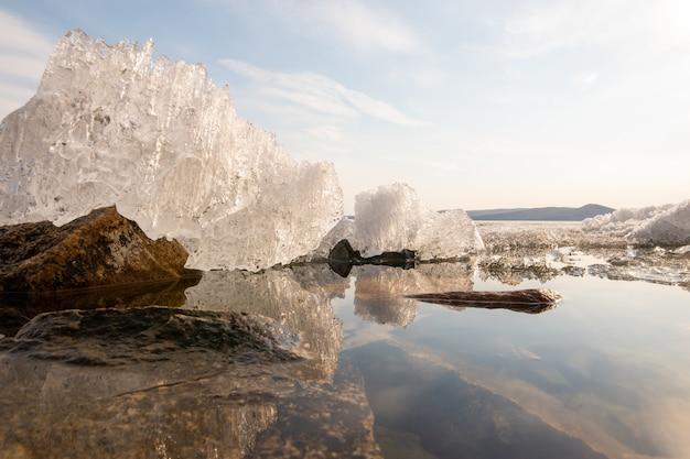 Derretimento do gelo no lago da primavera, reflexo do gelo na água, época antes do pôr do sol.