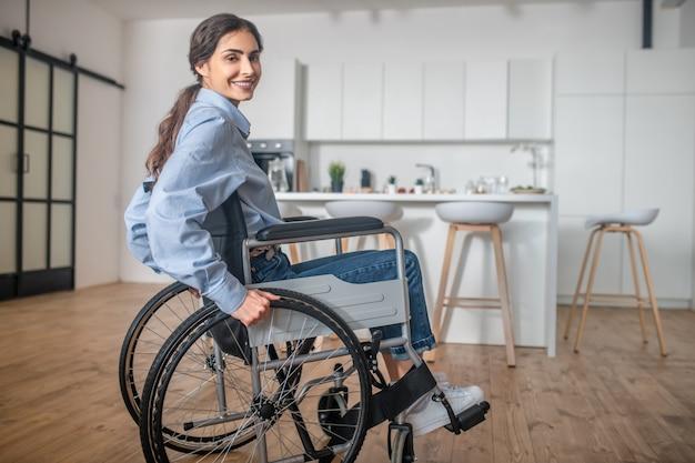 Desabilitado. uma jovem sorridente, sentada em uma cadeira de rodas