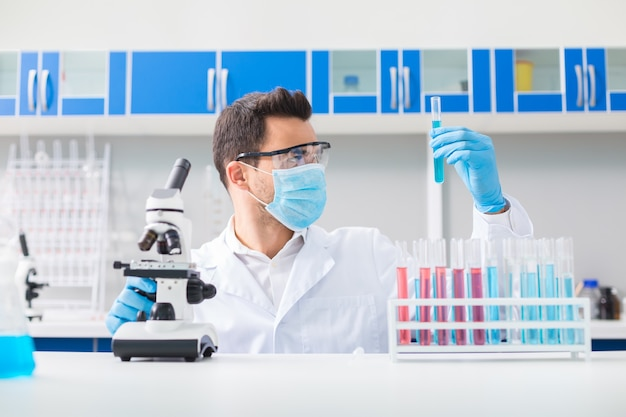 Desafio científico. homem bonito e agradável de laboratório vestindo óculos de segurança enquanto eleva o frasco e olha para ele