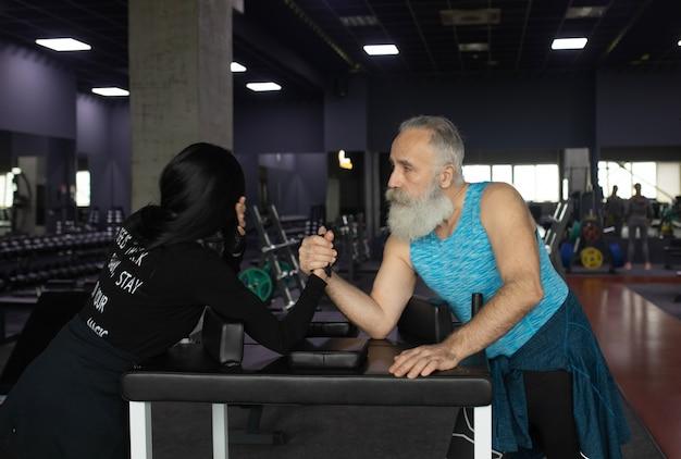 Desafio de queda de braço entre um casal de idosos.