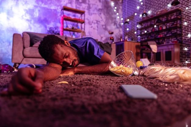 Desafio perdedor. homem barbudo quase morto estando extremamente bêbado e caído no chão, cercado de lixo e sobras