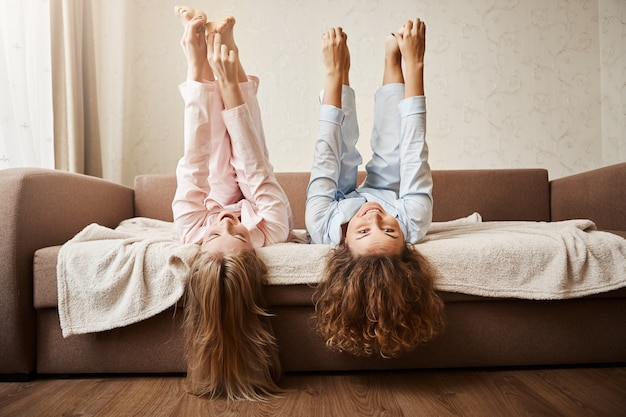 Desafio você a tocar os pés enquanto estava deitado. retrato de mulheres adoráveis, brincando e sendo infantil em casa, em roupas de dormir, deite no sofá, levantando os pés e tocando-o com as mãos de humor brincalhão