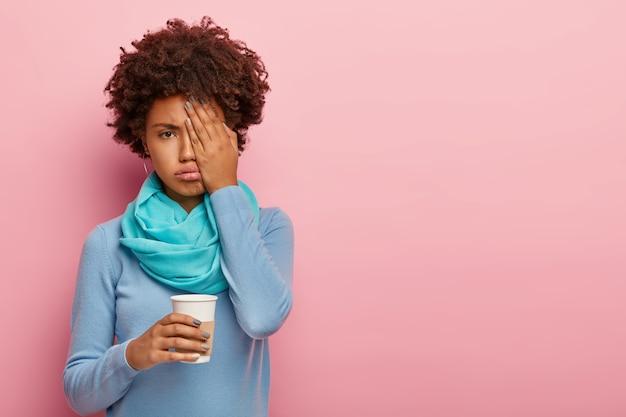 Desagradada, sonolenta e cansada, uma mulher afro cobre o rosto com a palma da mão, bebe café fresco ou cappuccino
