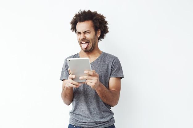 Desagradou homem africano mostrando a língua segurando o tablet.