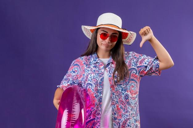 Desagradou jovem mulher bonita usando chapéu de verão e óculos de sol vermelhos segurando anel inflável, mostrando os polegares para baixo sobre parede roxa