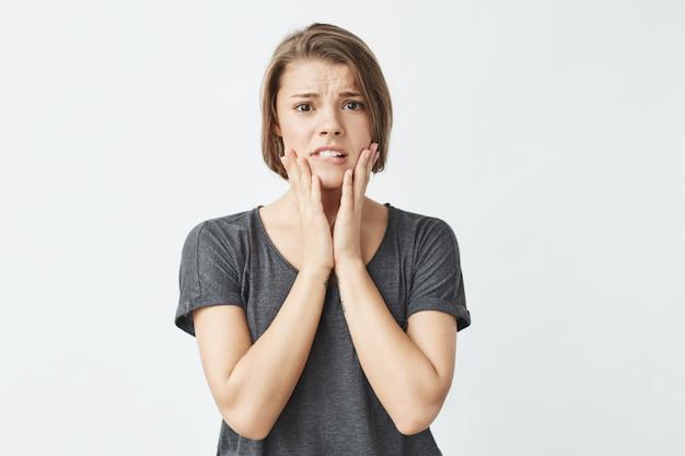 Desagradou menina bonita vergonha mordendo lábio segurando as bochechas.