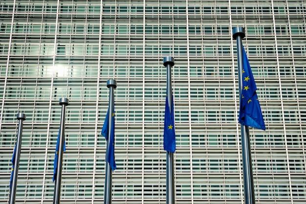Desamparadamente inclinando as bandeiras da união europeia da ue com o edifício da comissão europeia. bruxelas, bélgica