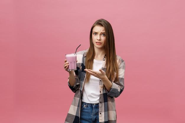 Desapontado jovem bebendo suco batido. retrato isolado.