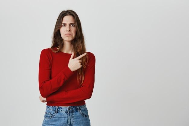 Desapontado, linda garota carrancuda reclamando, apontando o dedo no canto superior direito