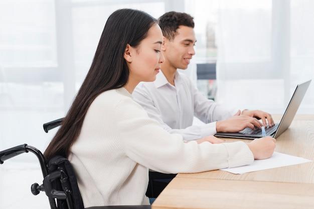 Desativado asiático jovem sentado na cadeira de rodas, trabalhando com seu colega usando o laptop na mesa no escritório